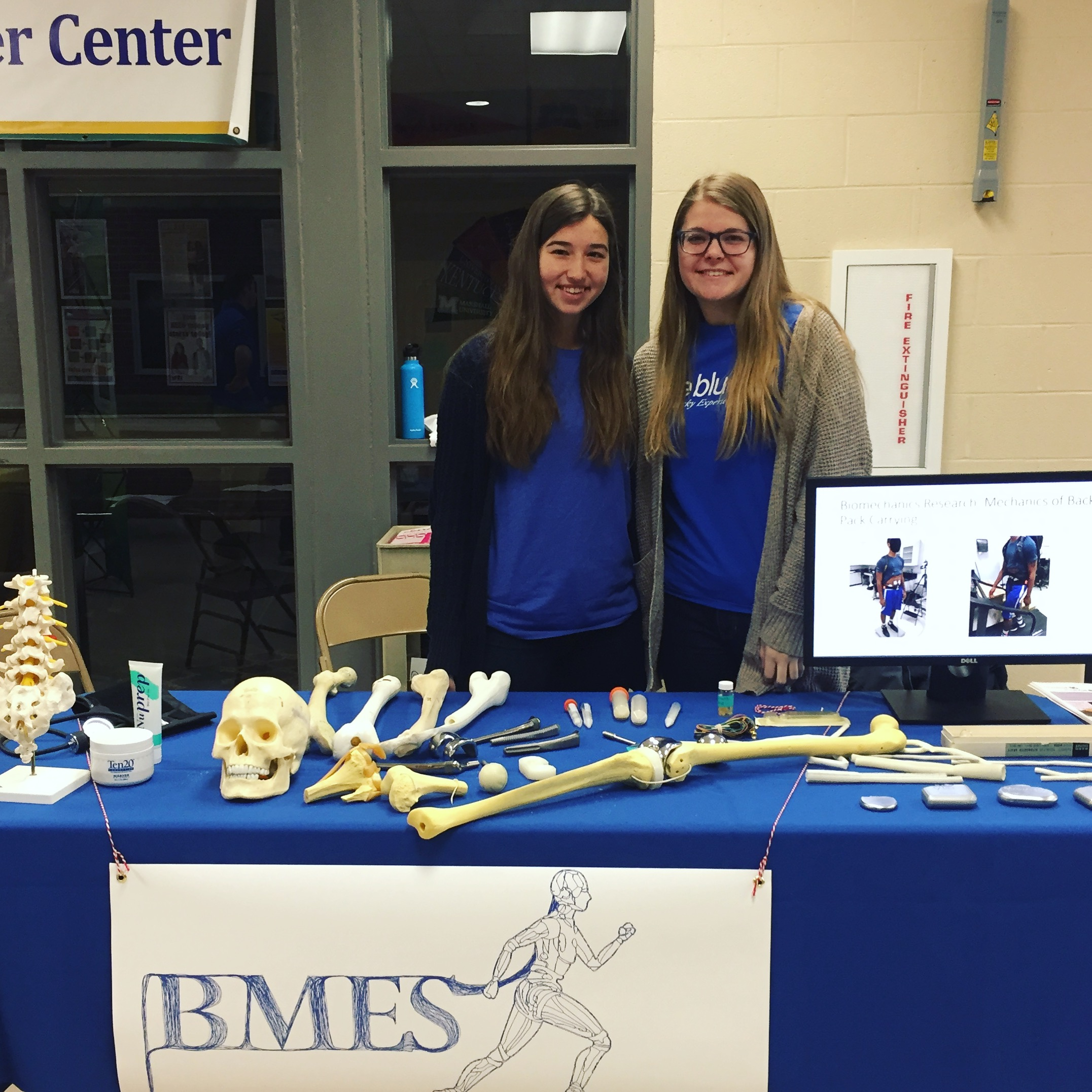 Undergraduate UK BMES members, Brittney Williams (left) and Madison Peppenhorst (right), behind the UK BMES science fair exhibit.
