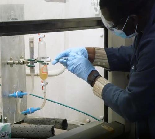 Reynolds Frimpong, senior research engineer at CAER, works on a carbon dioxide capture experiment.